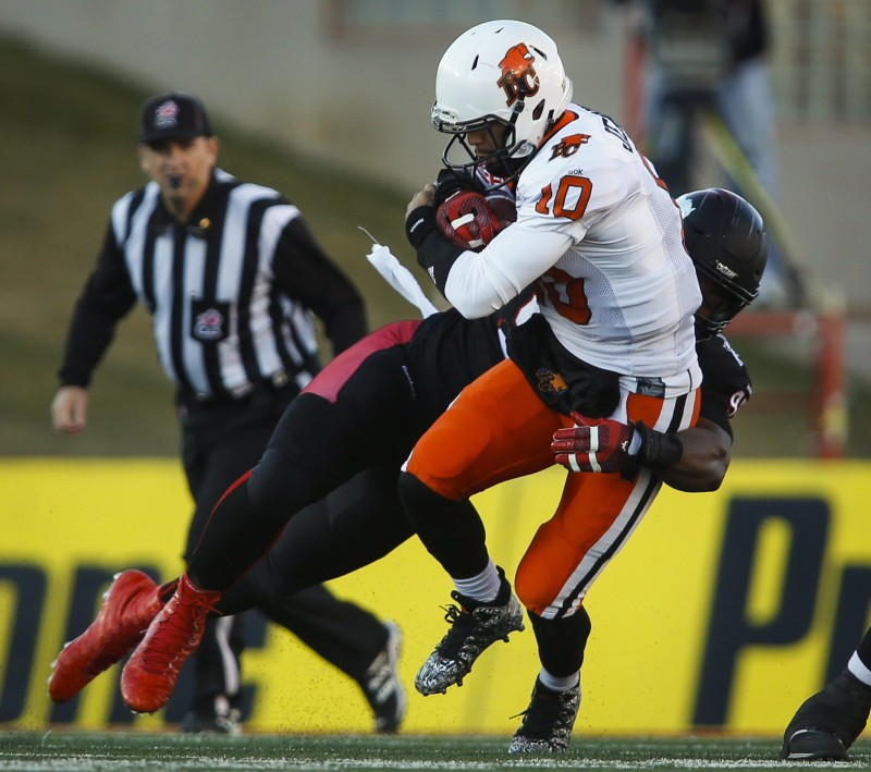 BC Lions quarterback Jonathon Jennings, right, is sacked by Calgary Stampeders' Freddie Bishop III during first half CFL western semifinal football action in Calgary, Sunday, Nov. 15, 2015.THE CANADIAN PRESS/Jeff McIntosh