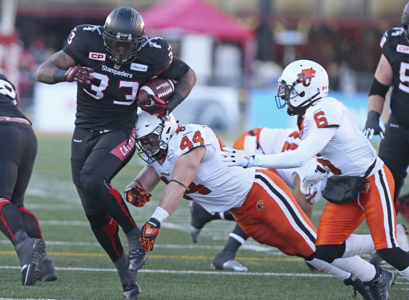 Calgary Stampeders Jerome Messam (33) scores against Adam Bighill (44) of the B.C Lions in first half CFL action west semi-final in Calgary on Sunday, November 15, 2015. (CFL PHOTO - Mike Ridewood)