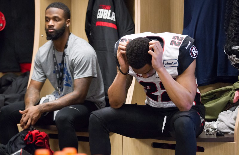 Ottawa Redblacks' Forrest Hightower, left, and Jeff Richards sit in the locker room after losing the 103rd Grey Cup to the Edmonton Eskimos in Winnipeg, Man., Sunday, Nov. 29, 2015. THE CANADIAN PRESS/John Woods