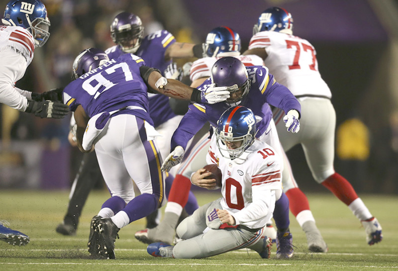 Giants quarterback Eli Manning (10) was sacked for an eight yard loss by Vikings defensive tackle Tom Johnson (92) in the second quarter Sunday night. Giants' Ereck Flowers, left, was penalized on the play for unnecessary roughness on the play.