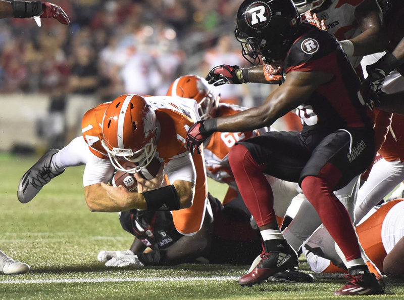 B.C. Lions quarterback Travis Lulay (14) makes a quarterback sneak against the Ottawa Redblacks during second half CFL action on Thursday, Aug. 25, 2016 in Ottawa. THE CANADIAN PRESS/Justin Tang