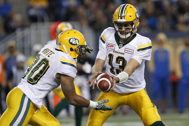 Edmonton Eskimos quarterback Mike Reilly (13) hands off to John White (30) during the first half of CFL action against the Winnipeg Blue Bombers in Winnipeg Friday, September 30, 2016. THE CANADIAN PRESS/John Woods