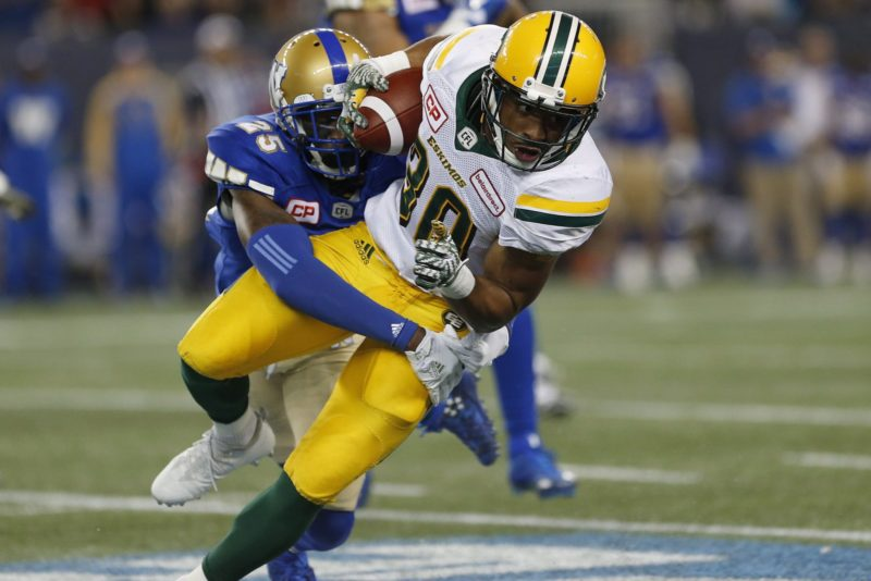 Edmonton Eskimos' John White (30) gets wrapped up by Winnipeg Blue Bombers' Bruce Johnson (25) during the first half of CFL action in Winnipeg Friday, September 30, 2016. THE CANADIAN PRESS/John Woods