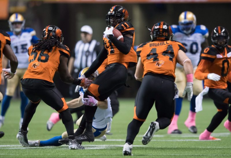 B.C. Lions' Mike Edem, centre, hangs onto the ball after intercepting a Winnipeg Blue Bombers pass during the first half of a CFL football game in Vancouver, B.C., on Friday October 14, 2016. THE CANADIAN PRESS/Darryl Dyck