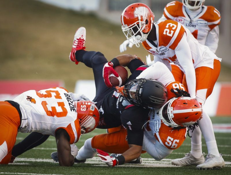 B.C. Lions' Alex Bazzie, left, Solomon Elimimian, right, and Anthony Gaitor, top right, bring down Calgary Stampeders' Lemar Durant during first half CFL western final action, in Calgary on Sunday, Nov. 20, 2016. THE CANADIAN PRESS/Jeff McIntosh